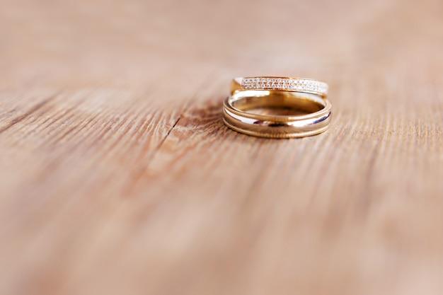 みすぼらしい木製の表面にダイヤモンドと黄金の結婚指輪のペア