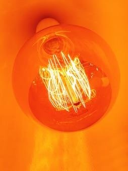 昔ながらの電球とシャンデリア。グローアーフィラメントとヴィンテージの電球。白熱、レトロなデザイン。