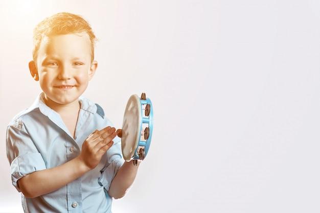 Веселый мальчик в синей рубашке держит бубен и улыбается