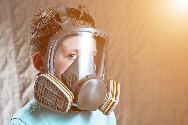 Портрет мальчика в легкой футболке с противогазом
