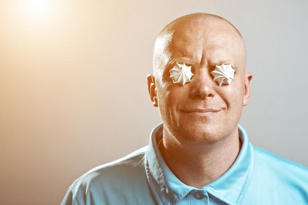 青いシャツを着たハゲの残忍な男が彼の目にメレンゲを入れた