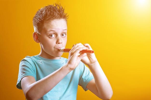 Мальчик в легкой футболке играет на трубе на цветном