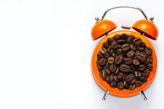 白い背景の上のオレンジ色の目覚まし時計で多くのコーヒー豆