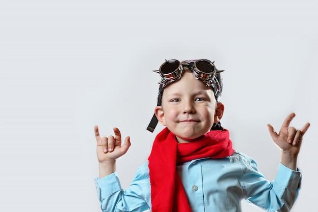 青いシャツ、赤いスカーフ、バイカーグラス、明るい背景にバンダナの少年