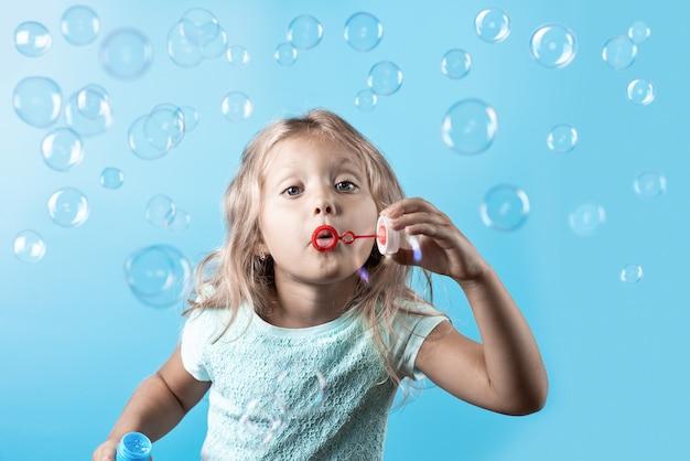 Милая девушка с вьющимися волосами, мыльные пузыри на синем