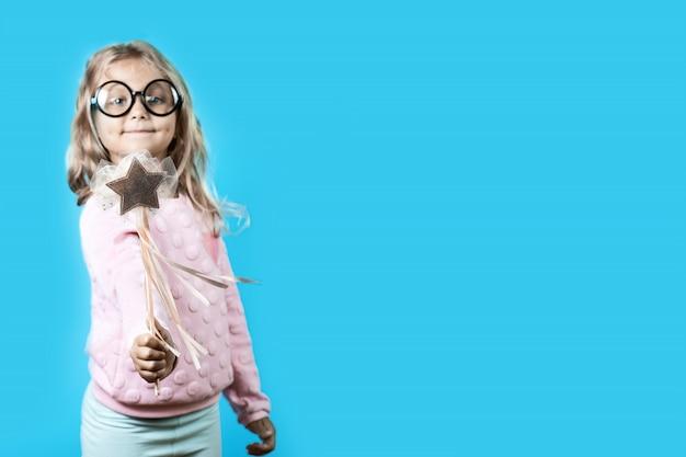 Девушка в очках и волшебная палочка произносит заклинание на синем