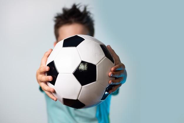 Мальчик в синей футболке держит футбольный мяч в руках, закрывая голову на синем фоне