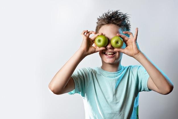 Мальчик в синей футболке подносит к глазам два зеленых яблока и смеется на светлом фоне