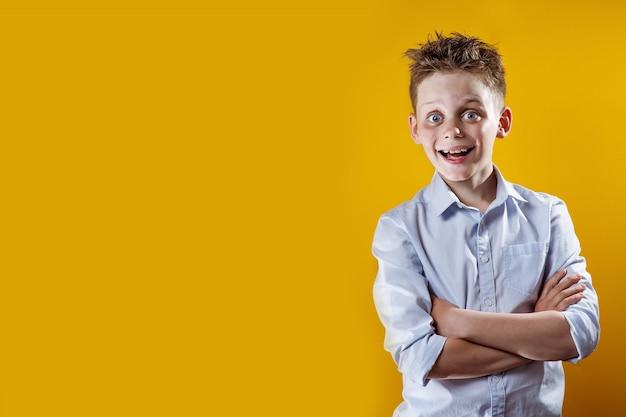 Веселый мальчик стоит и улыбается в легкой рубашке