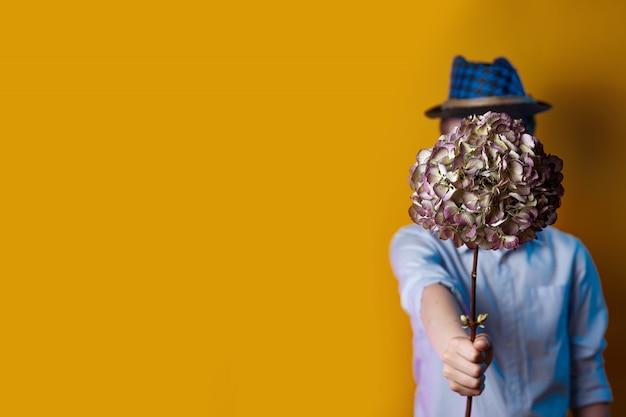 Человек в шляпе держит букет перед его лицом