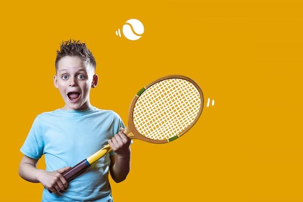 Мальчик в легкой футболке с теннисной ракеткой и мячом на оранжевом