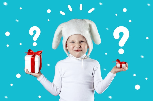 Мальчик в белом зайце пытается выбрать подарок на синем