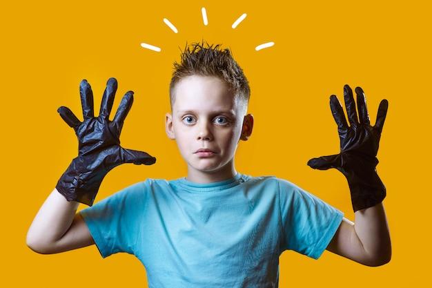Удивленный мальчик в черных перчатках и синей футболке на желтом фоне