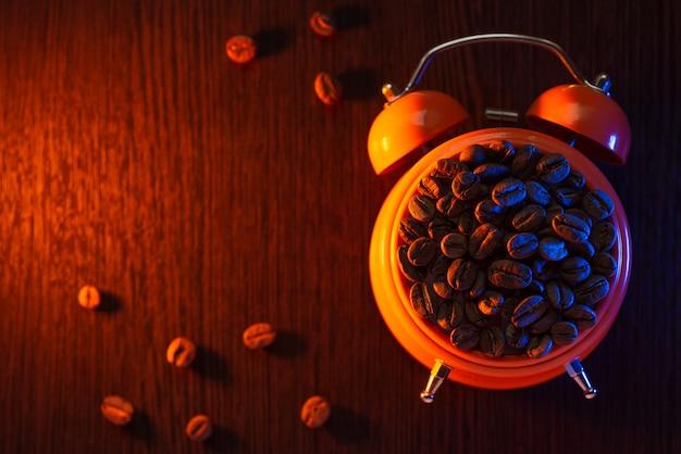 木製のテーブルの上のコーヒー豆とオレンジ色の目覚まし時計