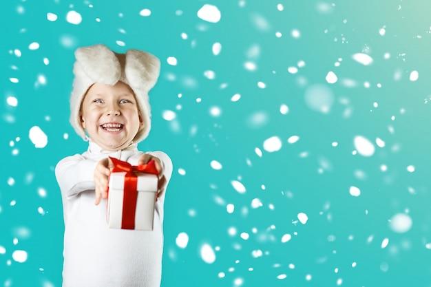 白いウサギの衣装を着た陽気な男の子は赤いリボンで贈り物をします。雪が降っている