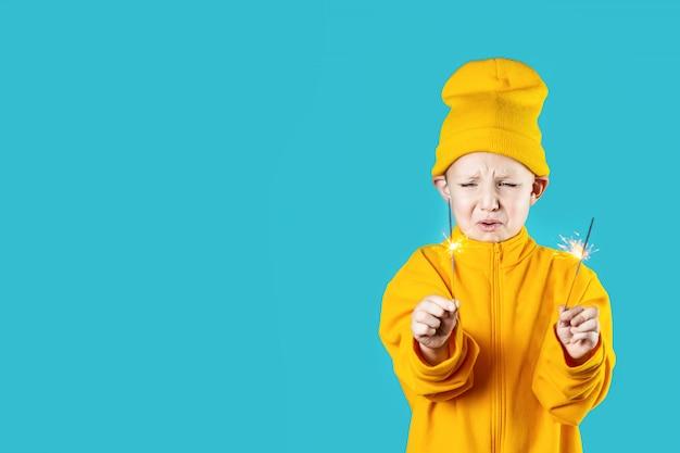 Маленький испуганный ребенок в желтой шляпе и куртке держит в руках горящие бенгальские огни на синем фоне