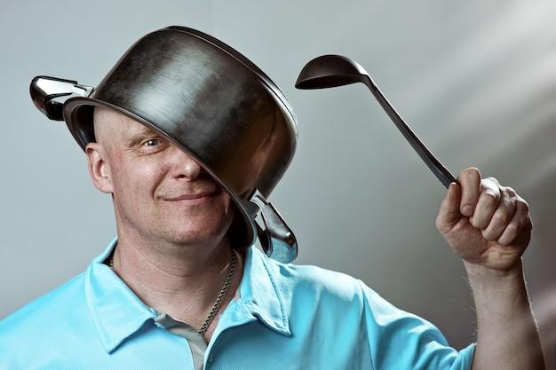 彼の頭に鍋と彼の手にお玉を持つハゲ男