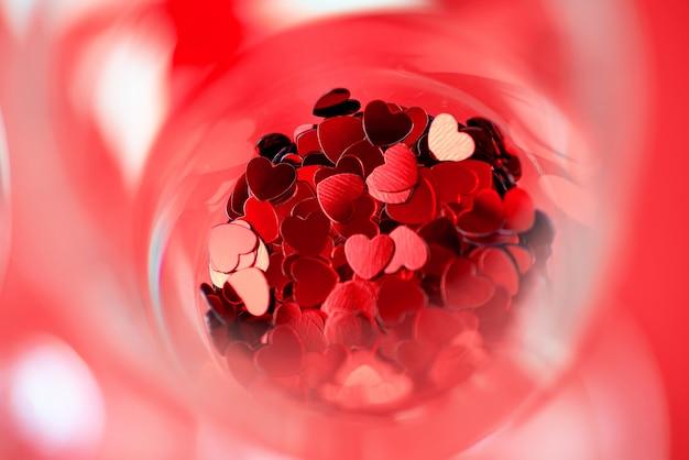 赤いハートがグラスに散らばっています。バレンタインデーのコンセプト。