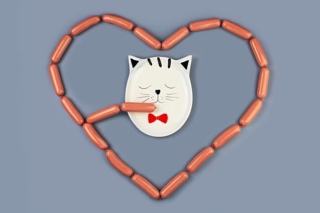 Тарелка с кошкой ест колбаски, разложенные вокруг нее сердцем. на сером фоне. концепция ко дню святого валентина