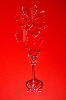 赤い背景の割れたガラス。ハート型の破片。