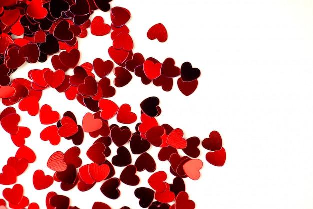 赤いハートは明るい背景に散らばっています。バレンタインデーのコンセプト。