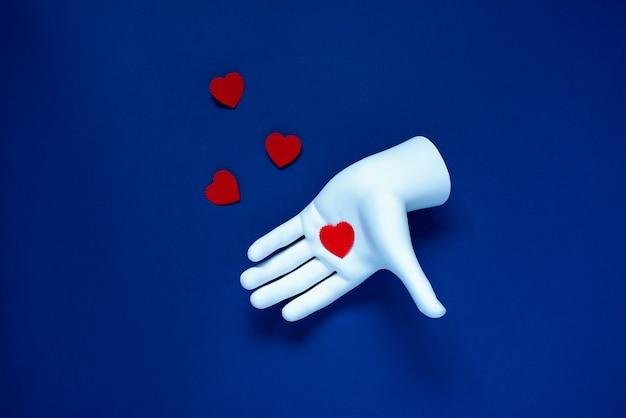 白い手に赤いハートがあります。青い古典的な背景に。バレンタインデーのコンセプト