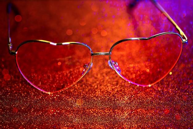 Сердцевидные очки на красном фоне с боке. день святого валентина