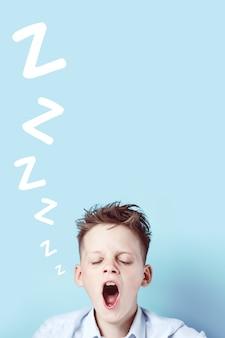 Мальчик в футболке устал, хочет спать и зевает