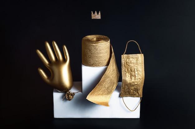 Золотая перчатка, туалетная бумага и маска на белом кнехте. концепция на тему тенденций коронавируса. черный фон