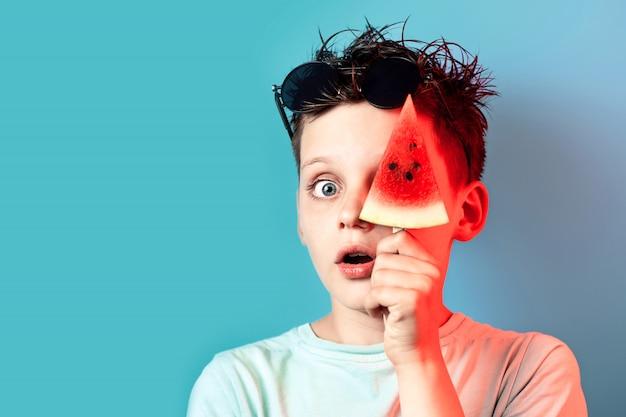 Мальчик в легкой футболке с арбузом на палочке закрывает один глаз