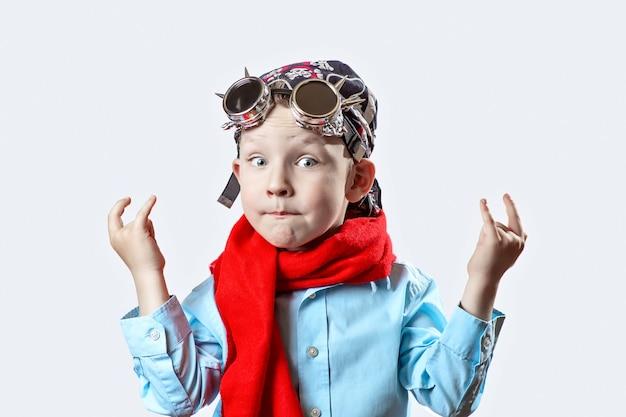 Мальчик в синей рубашке, красный шарф, байкерские очки и бандана на светлом фоне