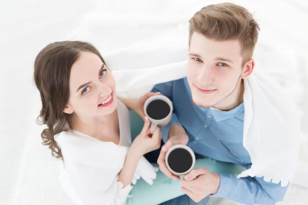 Молодая пара в любви дома с чашкой кофе