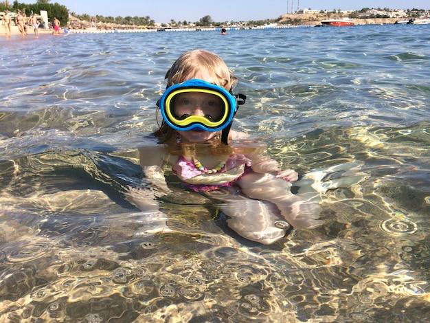 海での休暇ヨーロッパの外観の女の子はマスクで海を泳ぎます。