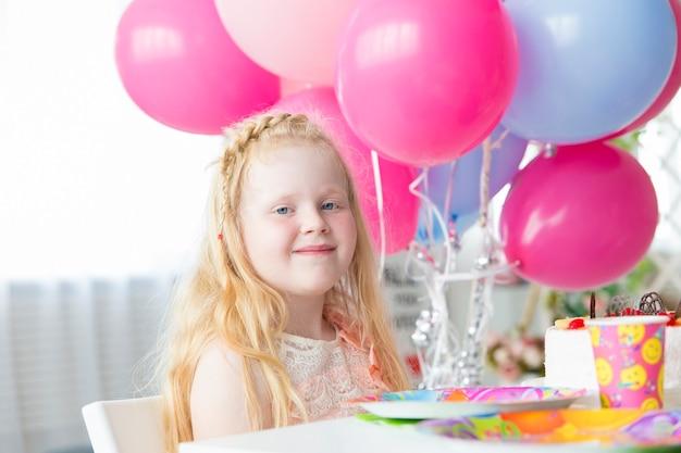 小さな女の子 - お祝いテーブルと明るくカラフルな風船の誕生日
