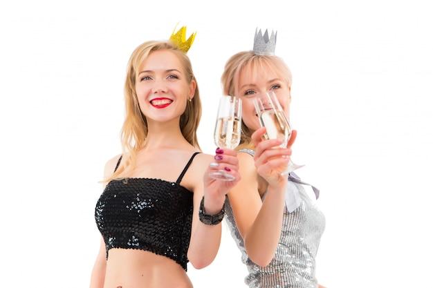 シャンパンのグラスと白のスタジオで、パーティーのドレスでポーズをとって二人の双子の女の子