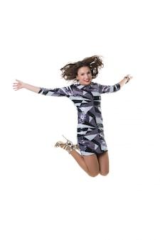 白のスタジオでジャンプ美しい幸せな女の子。買い物の喜び
