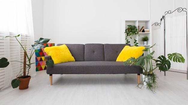 Современная однокомнатная квартира с живыми растениями. яркие цвета в интерьере. серый диван с желтыми подушками.