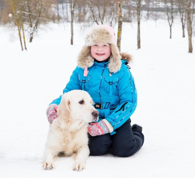 ペットを愛する - 少女は公園の雪の中でゴールデン・リトリーバーで休んでいます