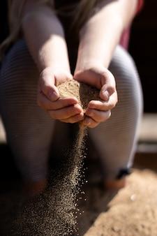 時間の経過 - 避けられない成熟の象徴としての子供たちの手の中の砂