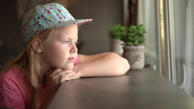 非標準的な外観を持つ美しい女の子が待っているカフェに座っています。