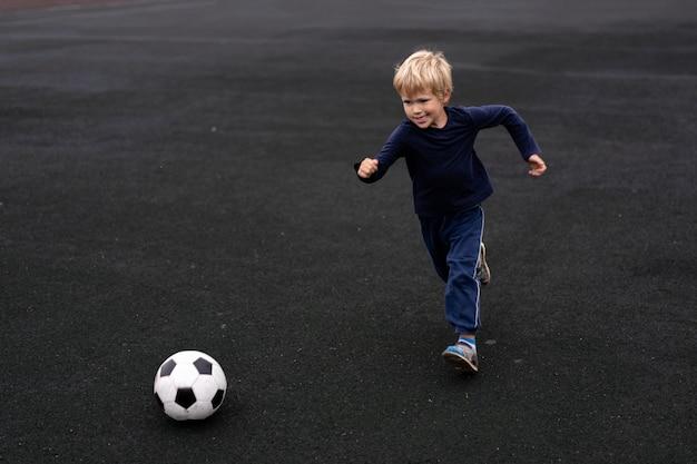Активный образ жизни в современном городе - маленький мальчик играет с футбольным мячом на стадионе