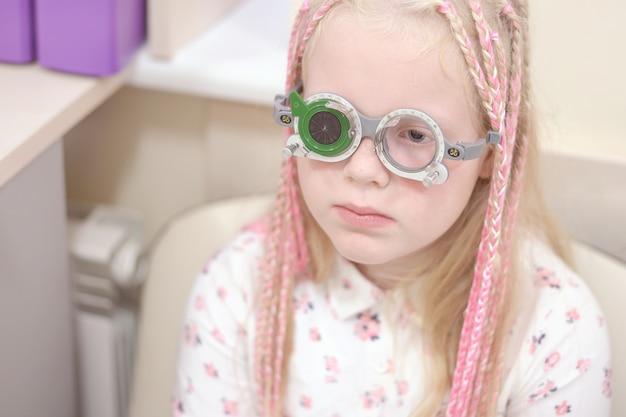 Проверка зрения. кавказская девушка с нарушениями зрения. лечение и реабилитация