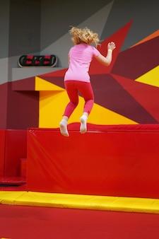 Счастливое детство современного ребенка в городе - девушка прыгает в батутном парке