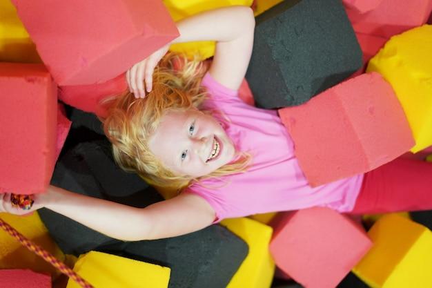 Счастливое детство современного ребенка в городе - девочка лежит в мягких кубиках в парке развлечений