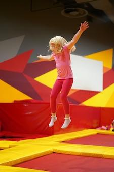 トランポリン公園でジャンプ女の子 - 都市の現代子供の幸せな子供時代