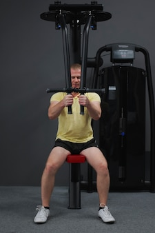 健康的なライフスタイル - ジムでスポーツをしている普通の若い男