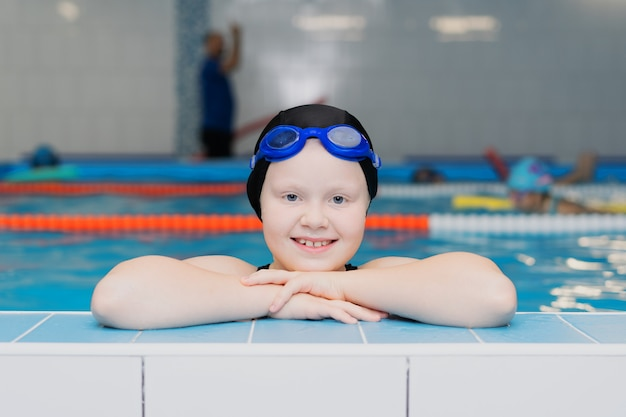 Уроки плавания для детей в бассейне - портрет красивой белокожей девочки в купальнике и шапочке для плавания