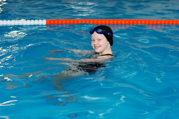 プールで子供のための水泳レッスン - 美しい色白の女の子は水で泳ぎます