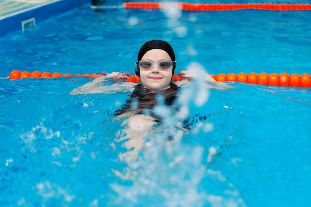 Уроки плавания для детей в бассейне - красивая белокурая девушка плавает в воде