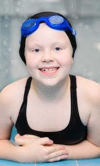 Портрет красивой девушки с белой кожей в купальнике и шапочке для плавания